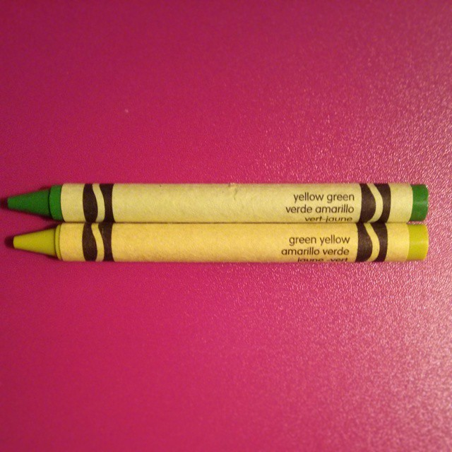 a photo of a yellow green crayon and a green yellow crayon