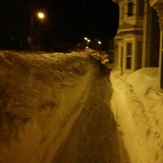 a photo of a giant snowbank next to a sidewalk at night