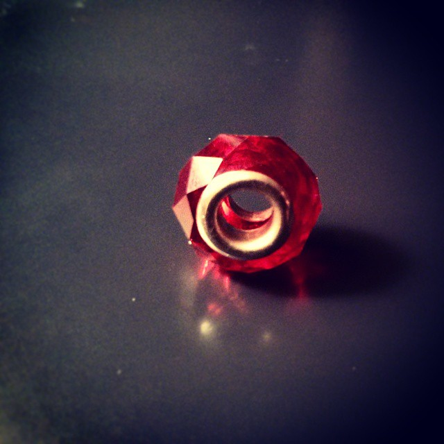a photo of a red faceted crystal pandora-type bead