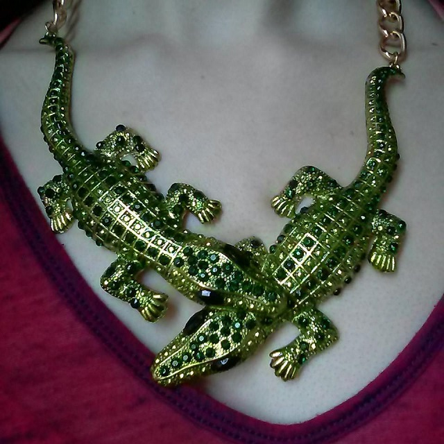 a photo of a necklace with two crocodiles covered in rhinestones