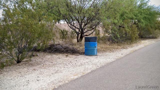 blue trash can alongside a path