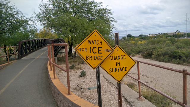 "caution signs that read ""watch for ice on bridge"" and ""change in surface"""