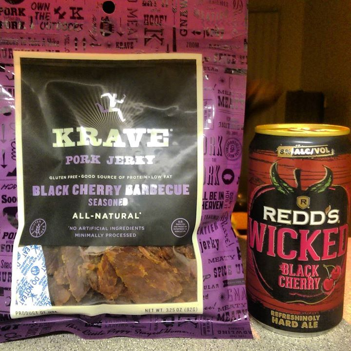 a photo of a package of a package of krave black cherry jerky and can of redd's black cherry ale
