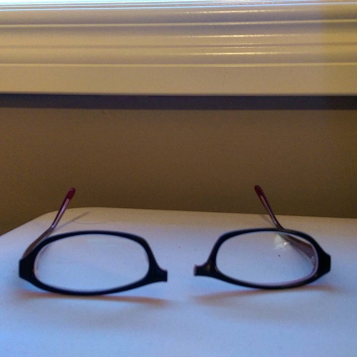 photo of a pair of glasses that has been broken in half