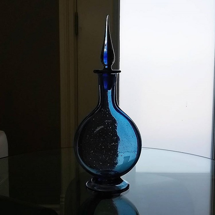 a photo of a glass decanter that is blue with a pointy stopper