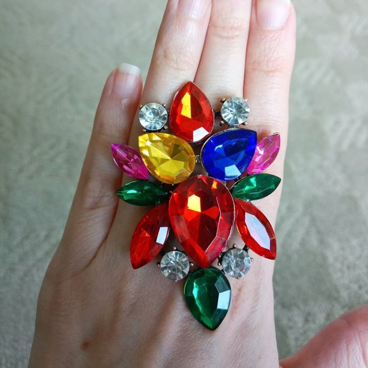 a photo of a hand wearing a giant jeweled ring with lots of jewels