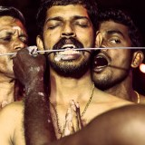 A devotee of the Hindu God Lord Murugan has his tongue pierced during the Thaipusam Festival