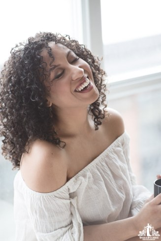 Natural light portrait of a young woman with natural curly hair laughing while drinking coffee