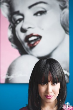 Portrait of a woman looking at the camera with an Andy Warhol reproduction Marilyn Monroe picture in the background