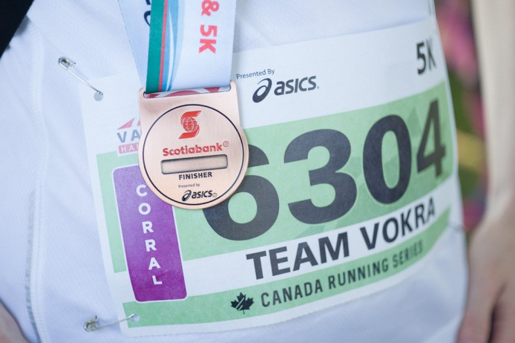 Team VOKRA running bib with a finisher medal from the Scotiabank Half Marathon in Vancouver