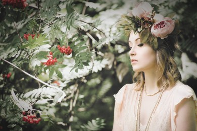 Natural light portrait of a young woman surrounded by greenery with red berries, wearing a flower crown looking away from the camera