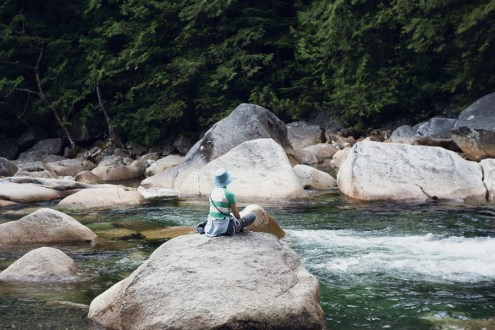 Image of a woman sitting on a boulder overlooking a river and waterfall