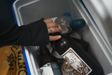 Image of a woman reaching for a beer in a cooler