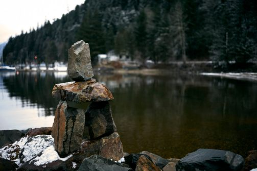 Moody image of a miniature Inukshuk on a breakwater at Harrison Lake