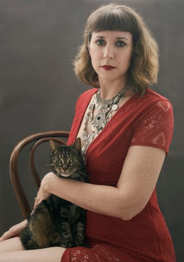 Portrait of a woman in a red dress with stacked silver necklaces and red lipstick holding a wide eyed tabby cat