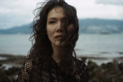 Outdoor natural light portrait of a woman on a rocky shoreline looking away from the camera as the wind blows her curls across her face