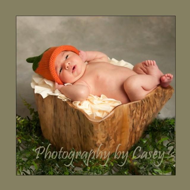 Photographer poses newborn with pumpkin hat