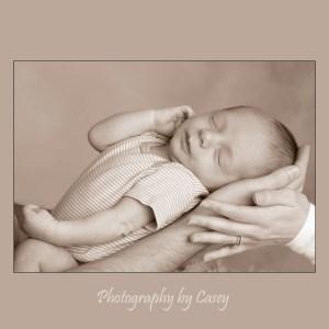 Dad's hand holding sleeping baby