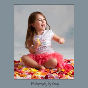 Photographer of girl in tutu playing in rose petals
