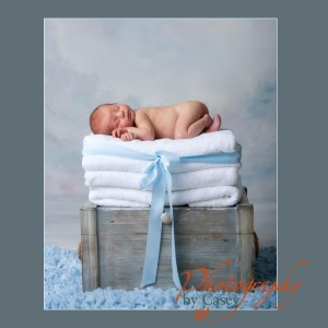 Newborn baby on stack of towels photographer