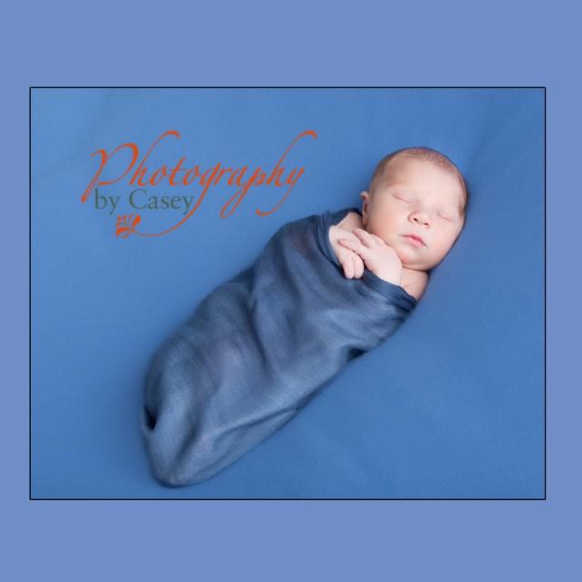 Newborn sleeping baby swaddled photography