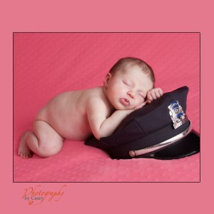 Police cap with sleeping newborn baby
