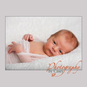 Newborn baby wrapped in cheesecloth photographer