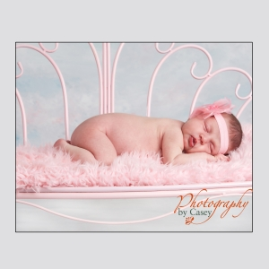 sleeping newborn baby on pink bench