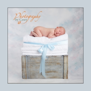 Stask of towels holding sleeping newborn baby
