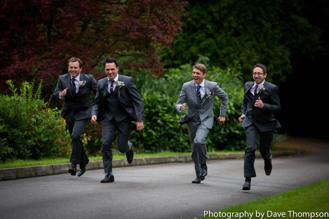 The best man chases the groomsmen up the winding driveway