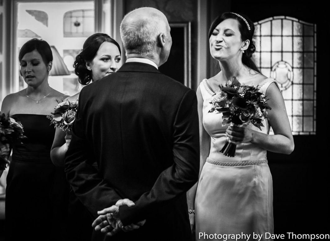 The bride playfully puckers up her lips towards her father