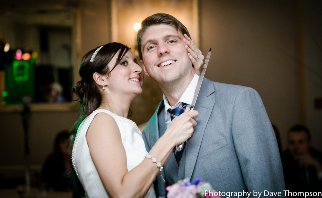 Cake cutting as the bride hold the knife to the grooms neck