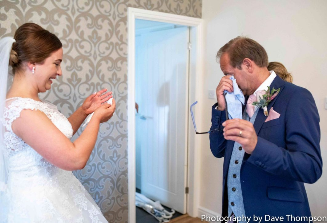 The father of the bride wipes his eye as he sees her for the first time