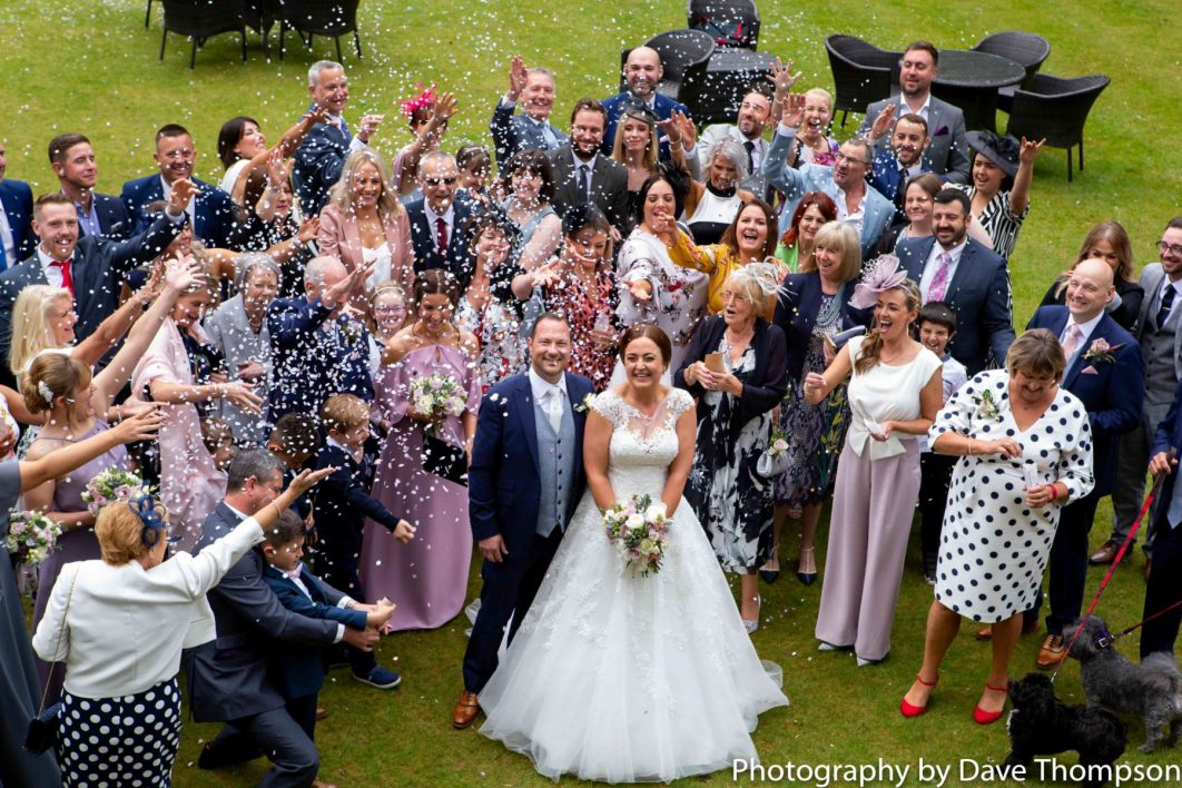 Confetti is thrown by the wedding guests