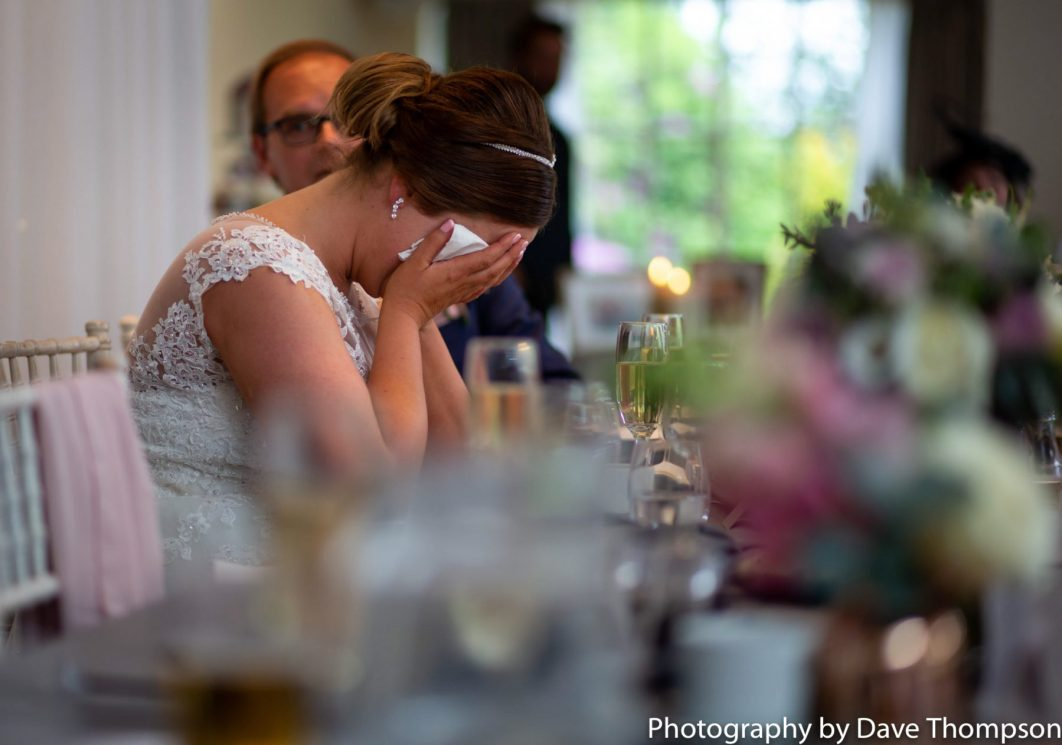 The bride sits with her head in her hands during the speeches