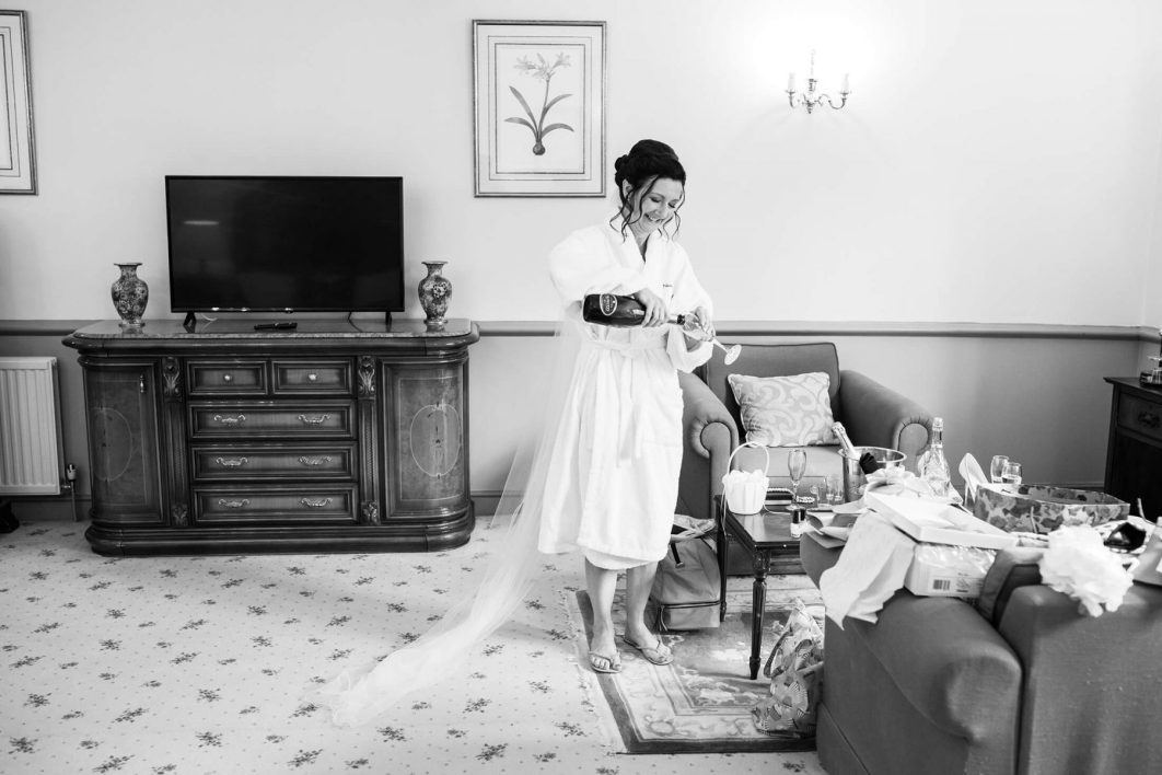 The bride urs herself a glass of champagne before her wedding