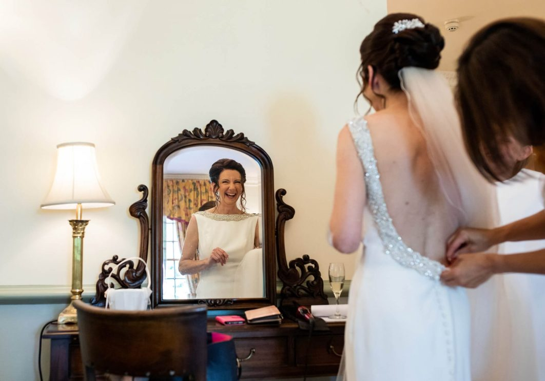 A bride is reflected in a mirror.