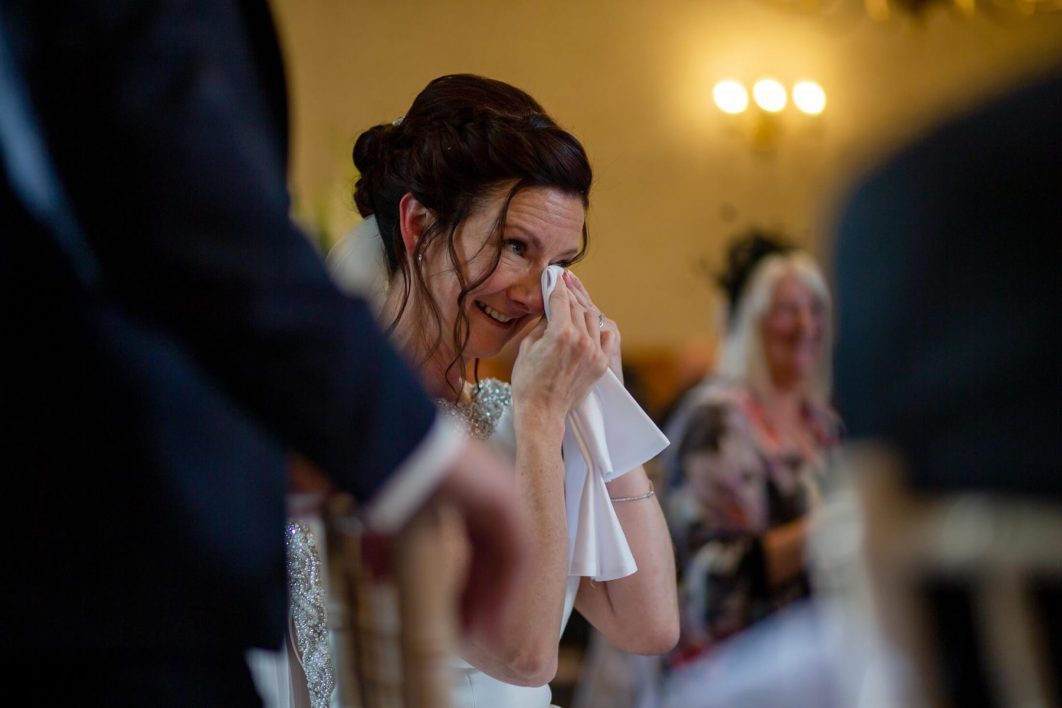 The bride wipes a tear from her eye during the wedding speeches.