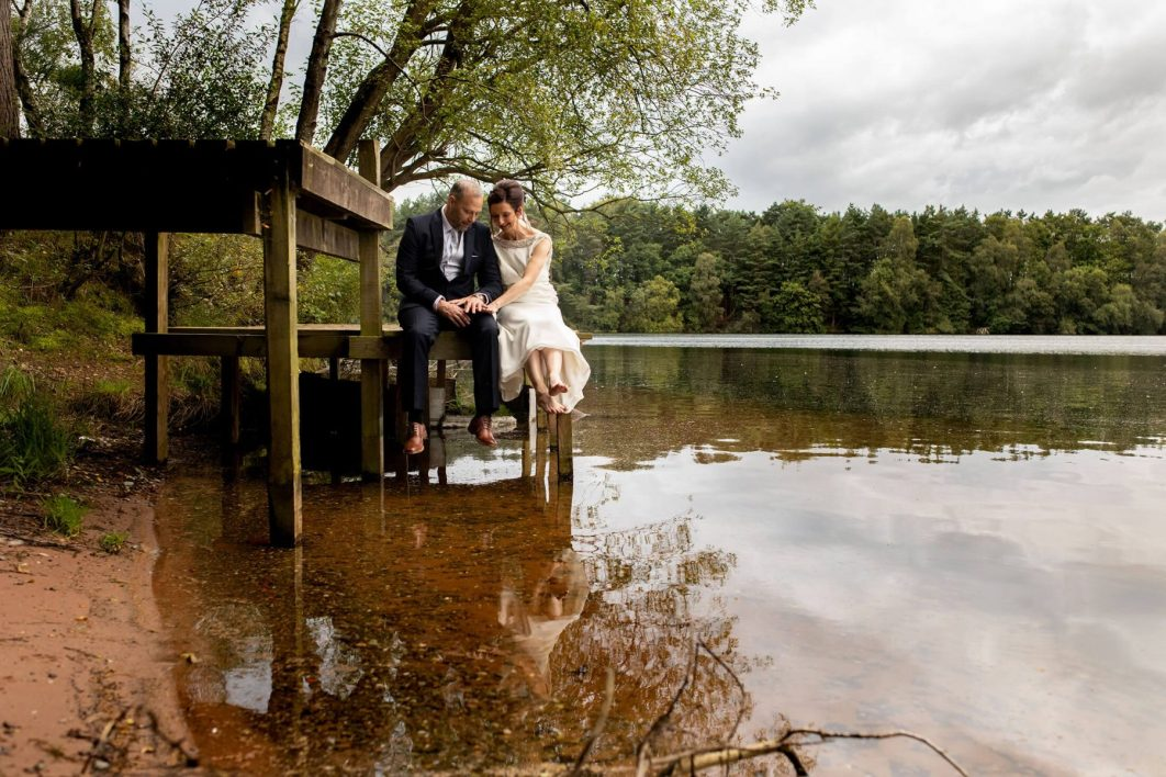 A bride and green sit by the 60acre lake at Nunsmere Hall