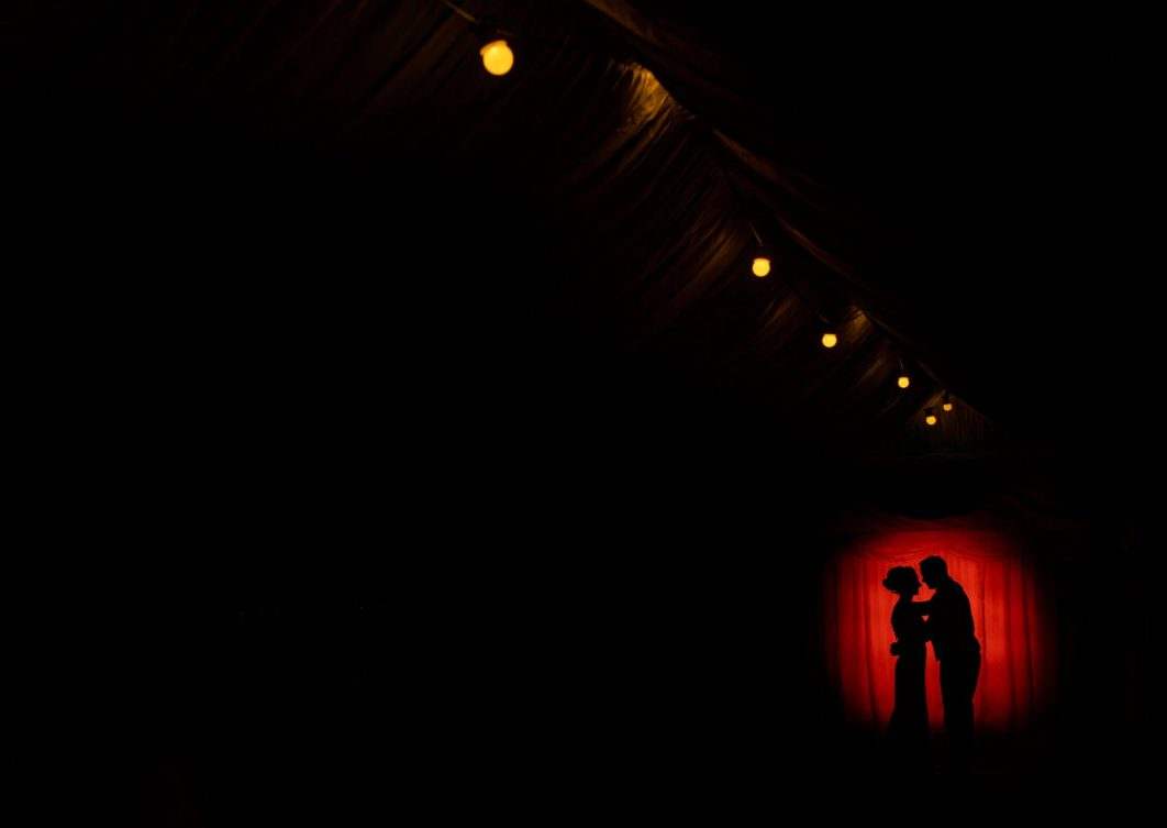 An off camera flash portrait of the bride and groom, silhouetted against a red circle background.