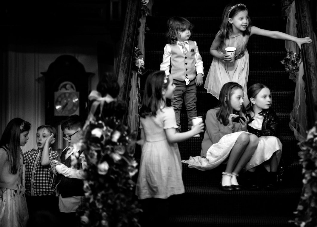 Children play on the stairs after a wedding at Hollin Hall Hotel in Bollington. Hollin House Hotel Wedding Photographer - an example of natural wedding photography