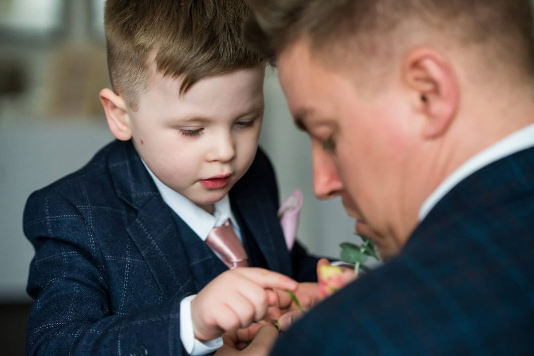 Hollin Hall Hotel Wedding Photographer - The grooms son looks at the grooms buttonhole flower