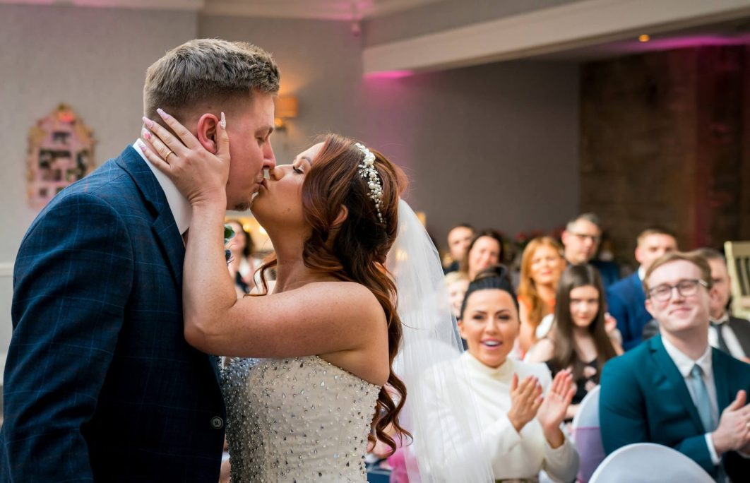 Hollin Hall Hotel Wedding Photographer - The bride and groom kiss during the ceremony