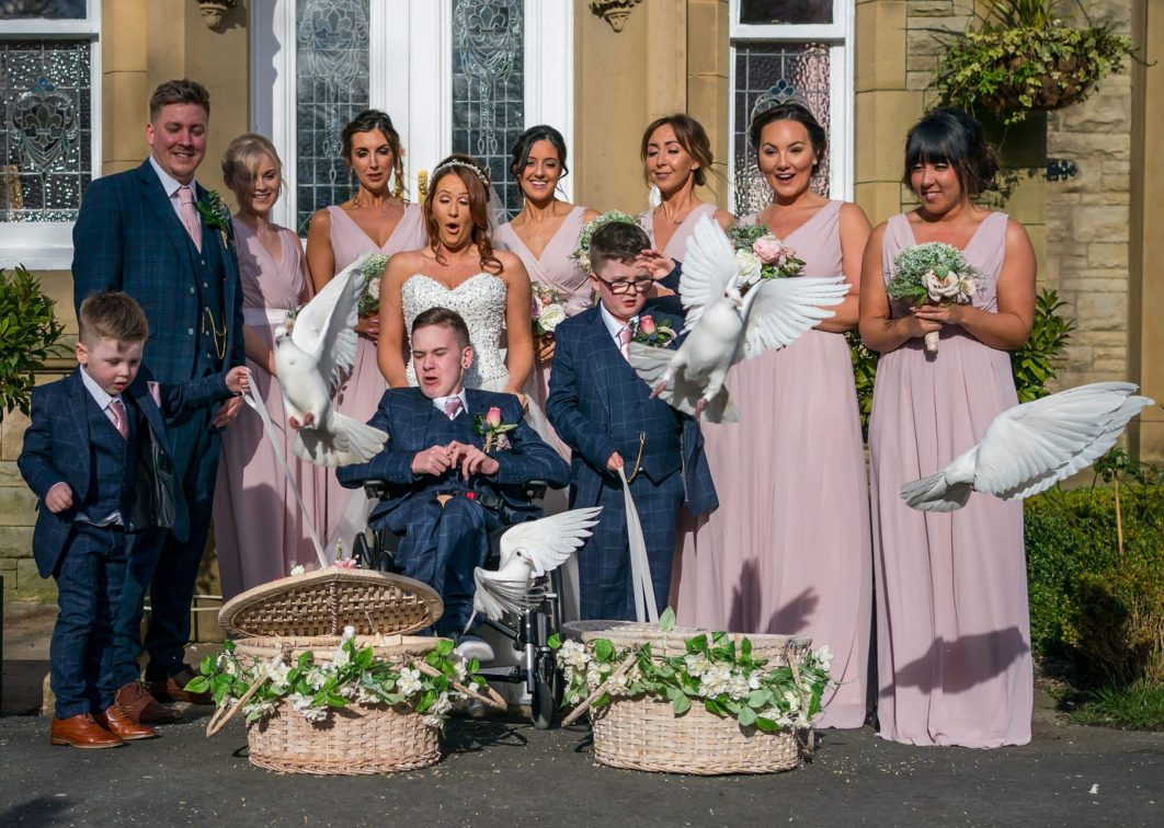 Hollin Hall Hotel Wedding Photographer - The bride and groom with family members as they release white doves into the sky