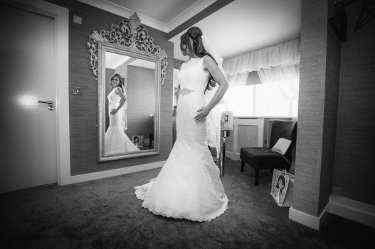 The bride checks her dress in a mirror