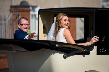 Bride and groom leave in their wedding car
