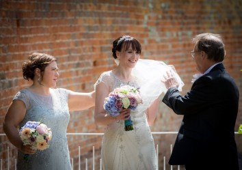 The father of the bride helps his daughter with her veil