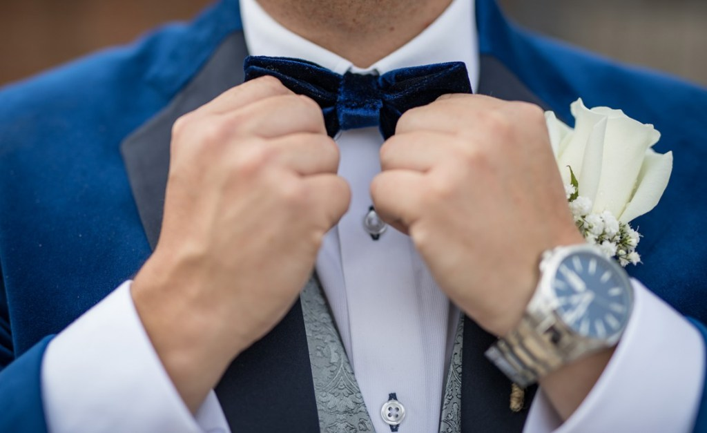 Groom adjusts his bow tie
