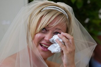 The bride wipes away a tear during her wedding ceremony