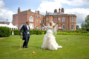 The brides celebrates beating the groom at a game of croquet